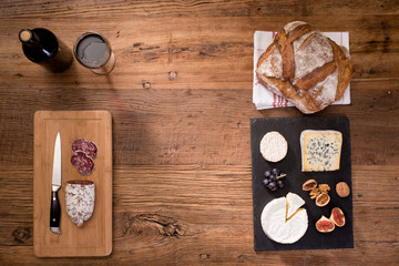 above overhead view flat lay still life of assortment various cheese and delicatessen with traditionnal bread and red wine on a old wooden table