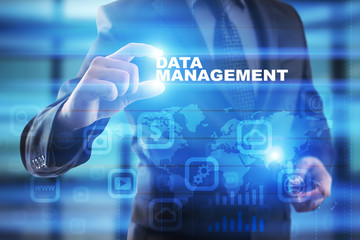 Businessman selecting data management on virtual screen.