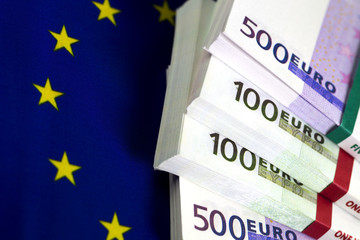 Bundles of euro bills. Two five hundred euro bundles and two hundred euro bundles. The Flag of Europe as background. Yellow stars circle. Close up image.
