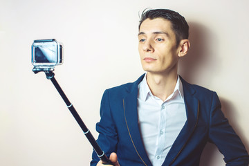 young business man in a suit taking selfie video