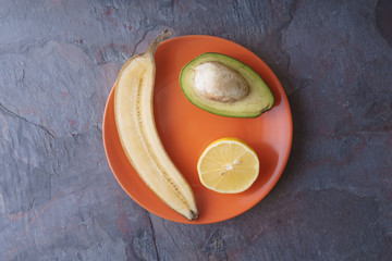 Avocado, lemon, banana halves lie on an orange plate on a slate