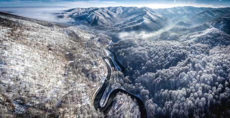 Panoramic image of a winding road from a high mountain pass in Transylvania, Romania with snow covered mountains in the background