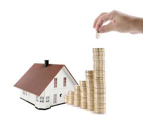 Male hand puts another Euro on savings for house investment isolated on white background.
