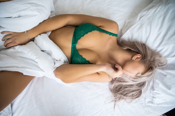 Above view of blonde sexy girl sleeping in white bed