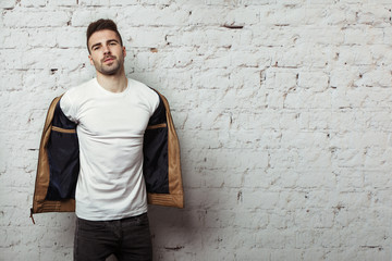 Handsome man in blank t-shirt taking off his leather jacket, white bricks wall background