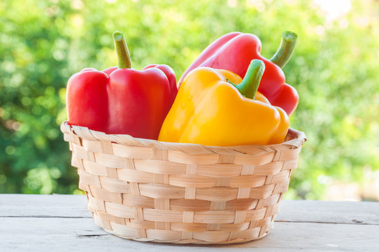 Fresh red and yellow bell peppers outdoors in a basket