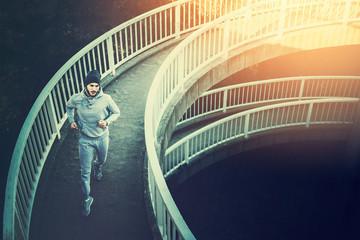 Man urban runner having intensive training outdoors in morning