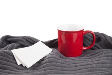 Farbige Tasse mit grauen Schal und Taschentücher