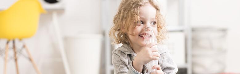 Happy little boy using inhaler