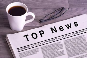 Eine Zeitung, Tasse Kaffee und eine Brille