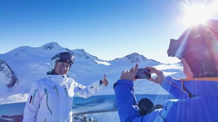 Pärchen macht ein Foto am Gipfel im Skigebiet