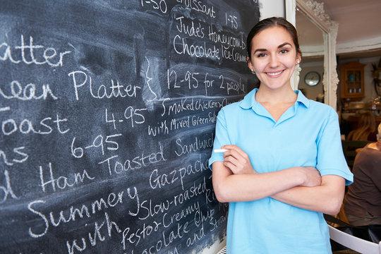 Waitress In Restaurant Writing Menu On Blackboard