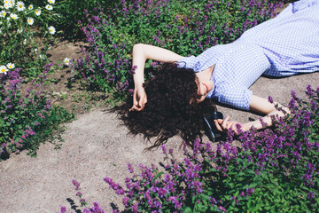 Curly young brunette in a blue dress with an old camera in her hands laying on the track in a green park, surrounded by flowers