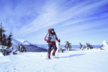 Winter hiking in the mountains on snowshoes with a backpack and