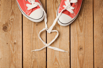 Valentine's day concept with heart shape shoelace and shoes. View from above