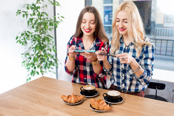 Two female friends photographing coffee with croissants on the table at the cafe