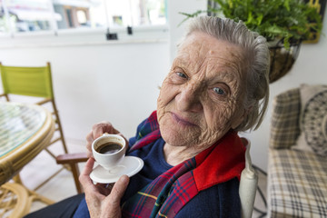 Senior old Turkish woman smiling to the camera and drinking Turkish coffee