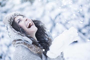 Frau im Winter pustet Schnee