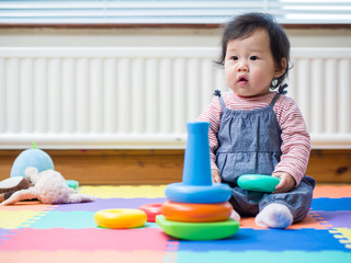 Adorable baby girl sitting on play mat and playing toy at home