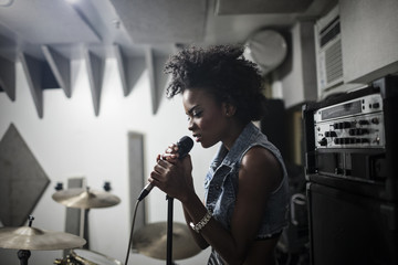 Young female singer performing in studio