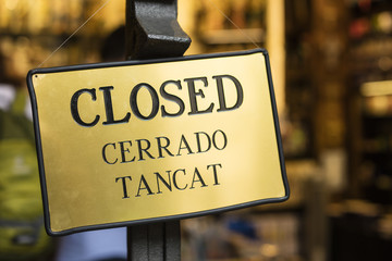 Detail of golden closed sign, written in English, Spanish and Catalan