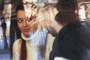 Young happy couple in cafe, view through a window