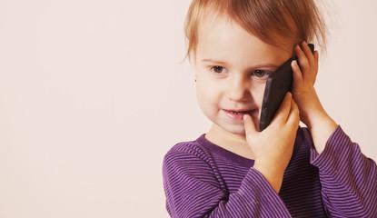 Little beautiful girl talking on the smartphone (communication,