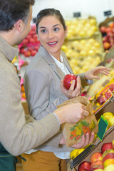 Woman buying apples, talking to grocer