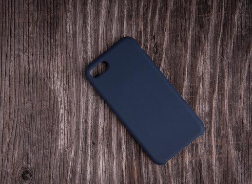 Black plastic phone case on rustic wood