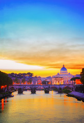St. Peter's cathedral over bridge and river in Rome at orange sunset, Italy