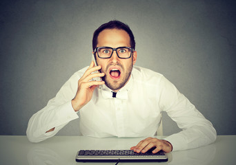 Shocked businessman talking on the phone while using computer