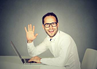 Man with laptop waving with hand saying hi to camera