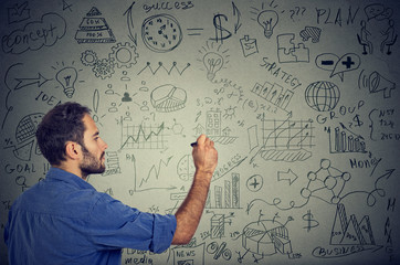 man writing on the wall business calculations plan.