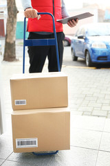 Courier with parcels and clipboard on doorstep