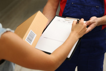 Young woman signing documents after receiving parcel from courier at home, closeup
