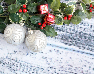 Silver Christmas balls with Holly leaves on wooden background