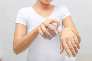 spray Bottle of perfume in hand  on white