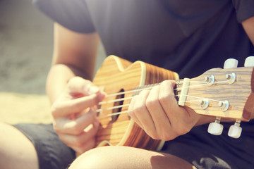 A man playing ukulele on the sandy beach in close up view. trave