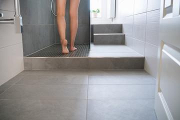frau geht in die dusche in ihrem modernen bad