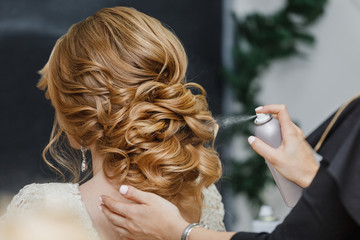 Master stylist makes the bride wedding hairstyle using spray lac