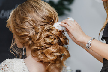Hair stylist or florist makes the bride a wedding hairstyle with