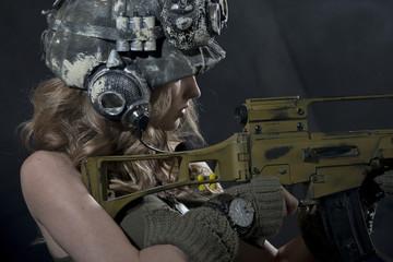 Beautiful young girl - soldiers, is shooting a machine gun