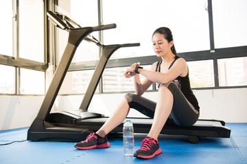sport woman rest on treadmill use smartwatch drinking water