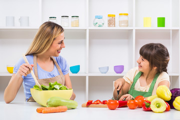 Happy mother and her daughter enjoy making healthy meal together at their home.