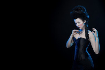 portrait of the actress brunette woman with high hair, necklaces and corset in old style on a black background