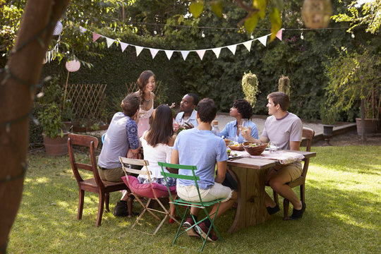 Woman Serving Food To Friends At Outdoor Backyard Party