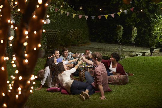 Group Of Friends Making A Toast At Evening Drinks In Garden
