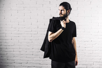 young bearded gothic hipster man standing on a brick wall background. a man dressed in black