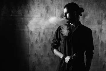 young bearded gothic hipster man smokes electronic cigarette. a man dressed in black