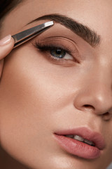 Beauty Woman Makeup. Closeup Of Beautiful Glamorous Sexy Woman Face With Smooth Skin Plucked Eyebrows And Metal Tweezers. Young Female Model Shaping Brows. Beauty And Skin care. High Resolution